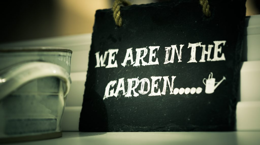 Blackboard with writing 'We are in the garden'